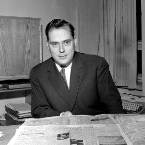 Toimittaja Paavo Noponen lukee lehteä työpöytänsä ääressä.