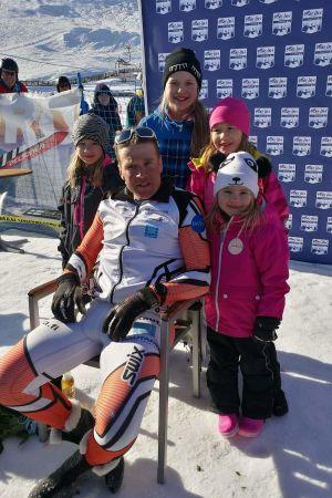 Hans Mäenpää ute i snön sittande på stol omgiven av döttrarna Wanja, Wilma, Wenla och Wilja. .