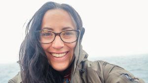 En kvinna med långt hår och glasögon. Hon står uppe på ett fjäll.