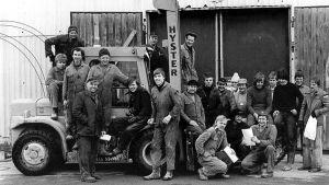 Män i arbetsoveraller poserar framför en traktor. Bilden är från slutet av 70-talet.