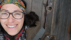 En kvinna med glasögon och en scarf knuten runt huvudet. Ligger på ett träunderlag och tittar in i kameran.