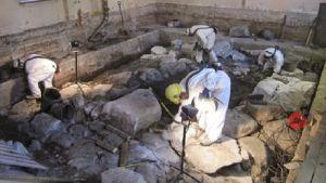 Arkeologerna måste klä sig i skyddskläder för att skydda sig mot den förstörda jorden.
