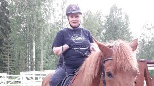 Nainen istuu hevosen selässä ja pitää ohjia. Naisen kädet on ranteen kohdalta amputoitu.