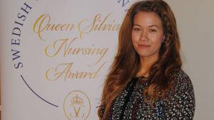 Maiju Björkqvist bredvid en skylt var det står Queen Silvia Nursing Award.
