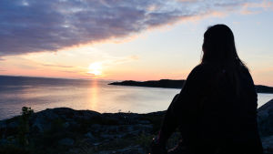 Siluetten av en kvinna som sitter på en klippa och tittar på solnedgången.
