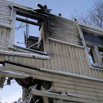 Det förstörda trähuset i Raunistula står kvar som en mörk påminnelse om branden.