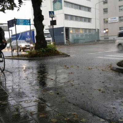 Cyklist iklädd regnkläder cyklar i kraftigt regn.