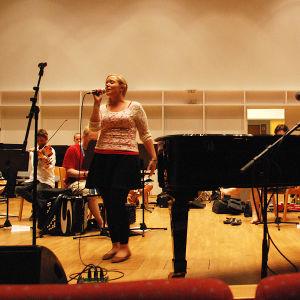 Nainen laulaa ja orkesteri säestää