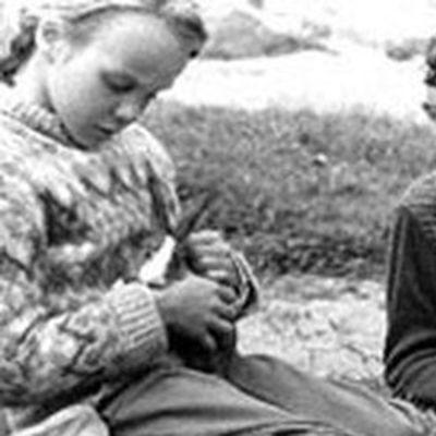 Tyttö ja poika leikkivät pupujen kanssa.