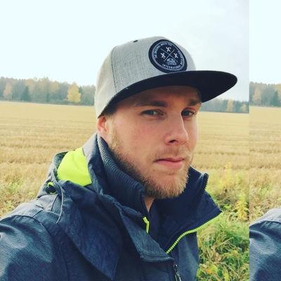 En man iklädd keps och blå jacka står ut på ett fält. Det ser ut att vara höst.