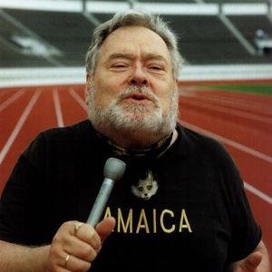 Jamaica-paitainen toimittaja Paavo Noponen stadionin juoksuradalla mikrofoni kädessään.