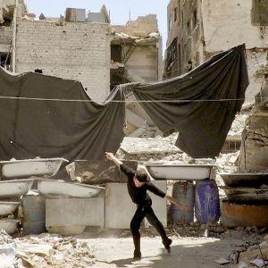 Ahmad Joudeh tanssii talojen raunioissa. Kuva dokumentista Tanssi tai kuole