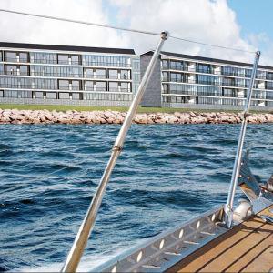 En skiss över en bostadsbyggnad med flera våningar vid havet. Det ser ut som om bilden är tagen på en segelbåt.