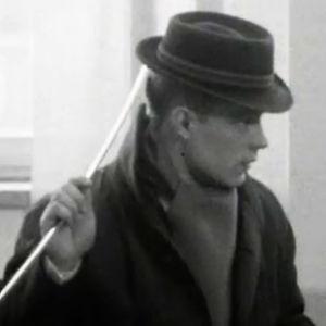 Mies nostaa hattuaan hattulusikalla.