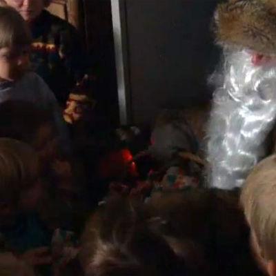 En julgubbe som delar ut julklappar