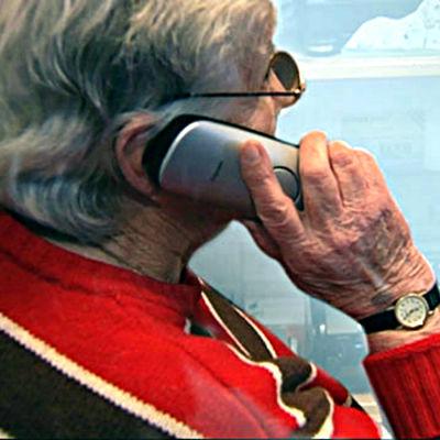 Äldre kvinna pratar i telefon.