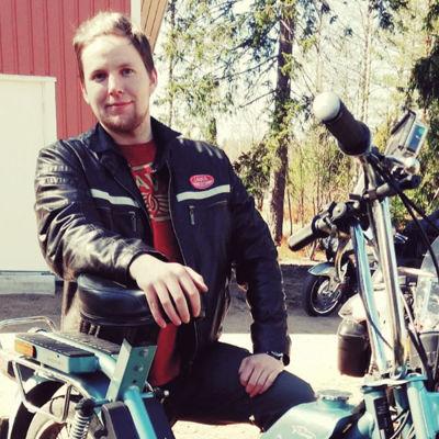 En man med blont hår och läderjacka står bredvid en gammal moped.