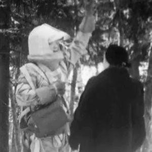 Avaruuspukuinen mies juttelee naisen kanssa kylänraitilla.