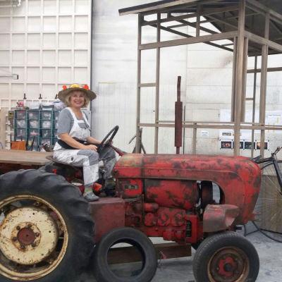 Lotta Kare sitter på en gammal traktor med en blommig hatt på huvudet