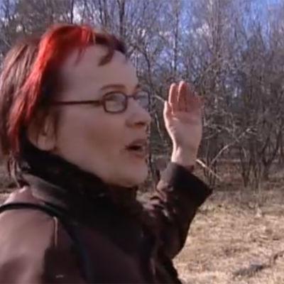 Tutkija Mirja Turunen osoittaa vanhaa koivua Kouvolan Veripellolla, jossa sisällissodan aikana vuona 1918 surmattiin joukko valkoisia.