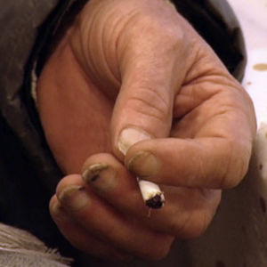 Hand med smuts under naglgarna håller i en cigarettstump.