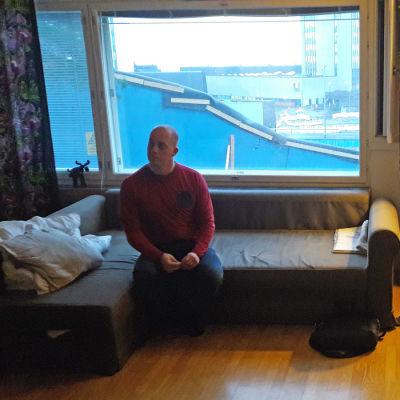 Joonas Ahola sitter på soffan.
