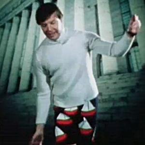 Uutistenlukija Heikki Kahila tanssii villahousuissa näytelmässä Villahousupakko, taustalla kuva eduskuntatalosta.