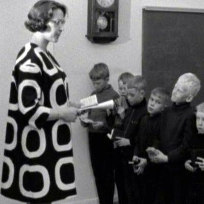 Päivä maalaiskoululla -ohjelmassa opettaja laulaa oppilaiden kanssa.