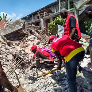 hjälparbetare gräver i rasmassor efter jordbävning