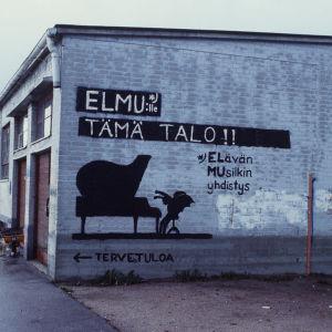 """Graffiti """"Elmulle tämä talo"""" Lepakkoluolan päädyssä"""