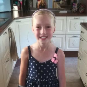 Blond flicka som ler iklädd hårband och blå klänning med rosa blomma vid axeln. Hon står i ett kök.