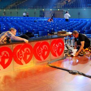 miehet korjaavat lavastetta
