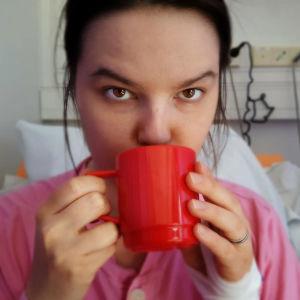 Pernilla Bergman sitter i sin sjukhussäng, ser in i kameran och dricker ur en röd mugg
