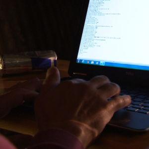 Kädet näppäimistöllä, näytöllä koodia