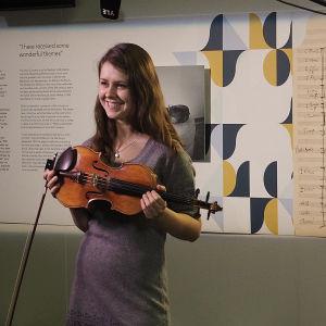 Poseeraus oman viulun kanssa Musiikkitalon aulassa, Sibelius-juhlavuoden näyttelyn siimeksessä.