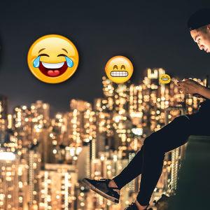 Mies istuu ja kirjoittaa matkapuhelimellaan. Kuvassa kolme emojia.