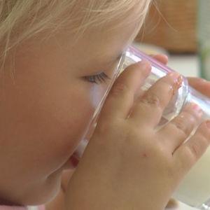 Liten flicka dricker mjölk ur ett glas.