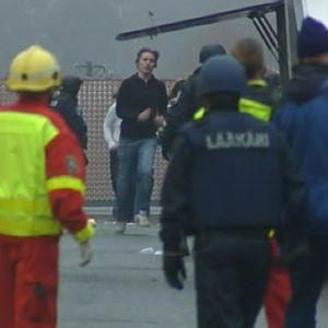 Uutiskuvaa Jokelan koululta koulusurmien päivänä. Ihmisiä juoksee koululta poispäin. Etualalla virkavaltaa ja lääkäreitä.