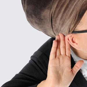 Nainen kuuntelee käsi korvalla