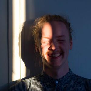 Viiksekäs mies hymyilee seinän edessä, auringonsäde osuu kasvoille.