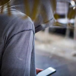 En ung person i munkjacka sitter lutad över en mobiltelefon.