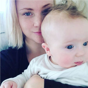 Carola Nordberg med sitt barn i famnen. Hon gömmer sig halvt bakom spädbarnets huvud och kikar försiktigt in i kameran.