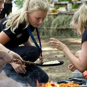 scoutflickor lagar mat över öppen eld