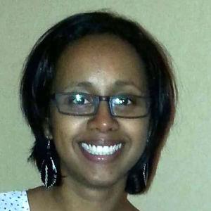 En kvinna med glasögon som ler stort.