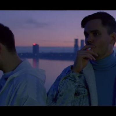 Två killar står och röker i solnedgången.