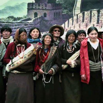 Tiibetiläisperhe poseeraa valokuvaajalle Kiinan muurin kuvan edessä