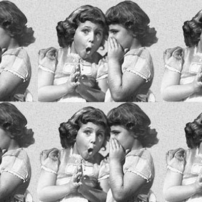 En flicka som viskar något till en flicka som ser förvånad ut.
