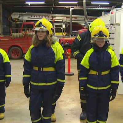 Unga brandkårister uppställda inomhus inför övning utomhus.