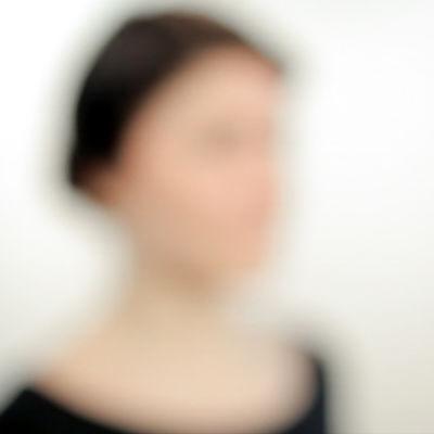 nainen seisoo valkoista taustaa vasten, epätarkka kuva
