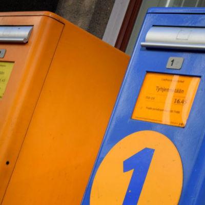 En orange andraklasspostlåda och en blå förstaklassbrevlåda.